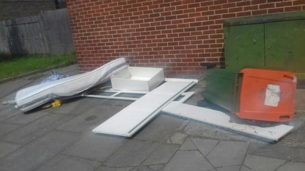 A mattress and dismantled bed frame with other household wastes dumped near block 71 to 79 Garvary Road E16 -2 Garvary Rd, London E16 3SF, UK