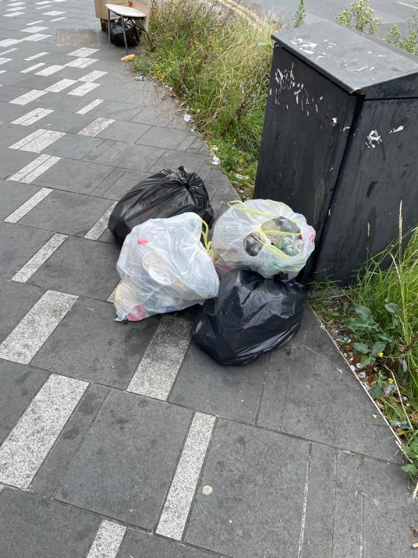 Trash on the sidewalk by a cabinet -131 The Grove, London E15 1EN, UK