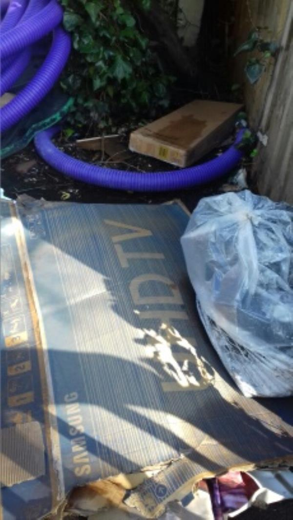 Cardboard boxes and a bag of wastes dumped at the rear of 75 Khartoum Road -5 Tunmarsh Ln, Plaistow, London E13 9ND, UK