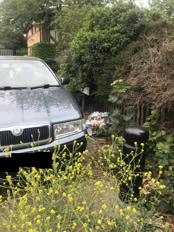 Bag of street cleansing shoved down the side by bushes -34 Magpie Close, London, E7 9DE