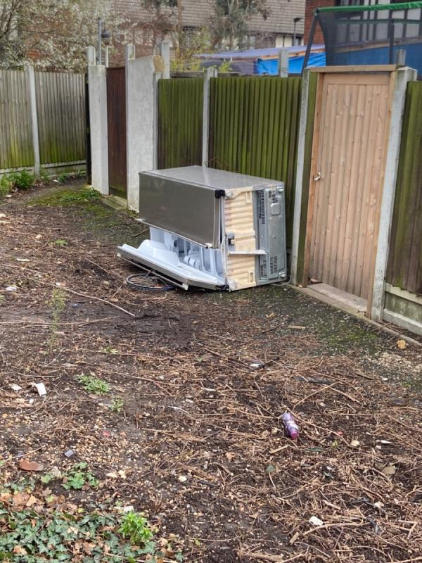 Large fridge dumped on open space by bus stop N on Woolwich Manor Way-2 East Ham Manor Way, London, E6 5PH