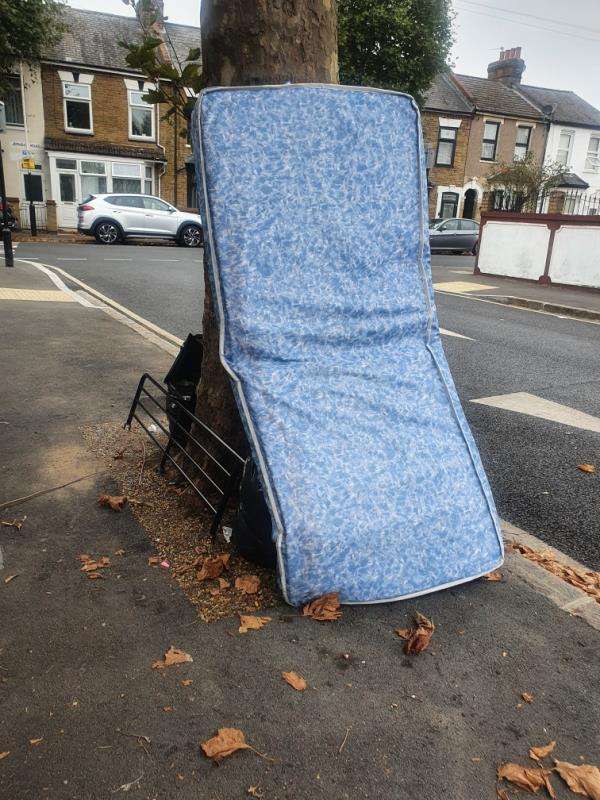 Mattress dumped on pavement by tree -61 Lansdown Rd, London E7 8NF, UK