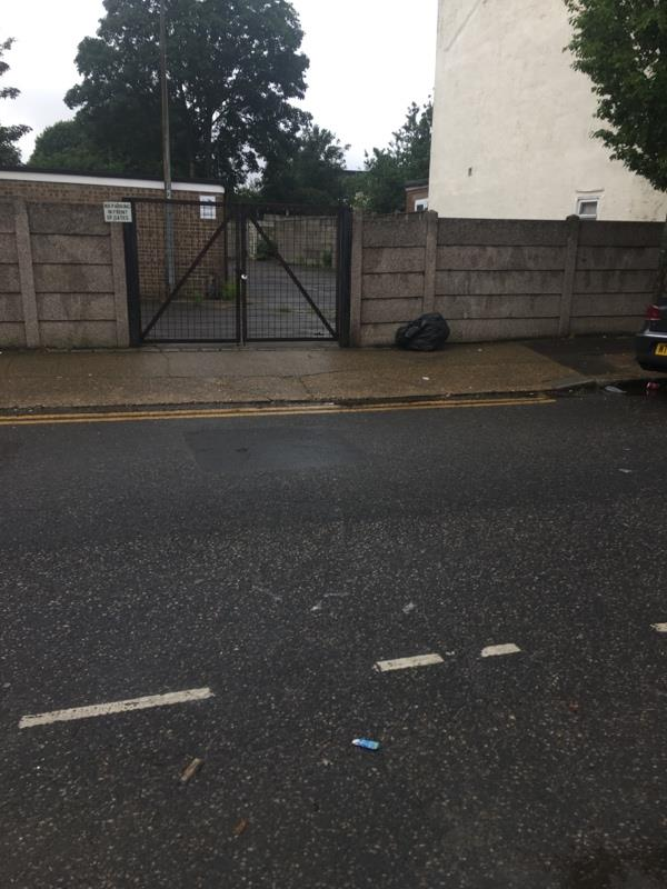 Black bag of rubbish dumped by garage gate -2 Dean St, Forest Gate, London E7 9BJ, UK