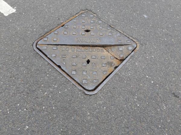 Cracked manhole cover on Grangewood Street close to junction with St Bernard's Road. -122 Grangewood St, East Ham, London E6 1HD, UK