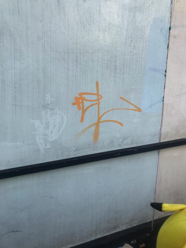 Orange spray painted tag is located on a magnolia painted wall on a pedestrian subway on Oldfield Lane North junction A40 Western Avenue Ub6 -1 Western Ave, Greenford UB6 9JP, UK