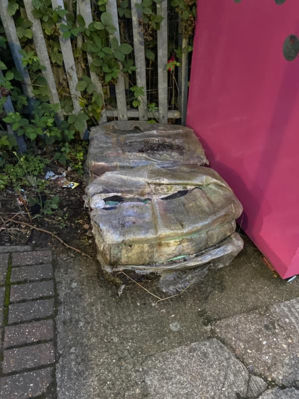 Two large bundles of soaking wet rotting clothes at Rayleigh Road recycling point -1 Rayleigh Road, North Woolwich, E16 2BE