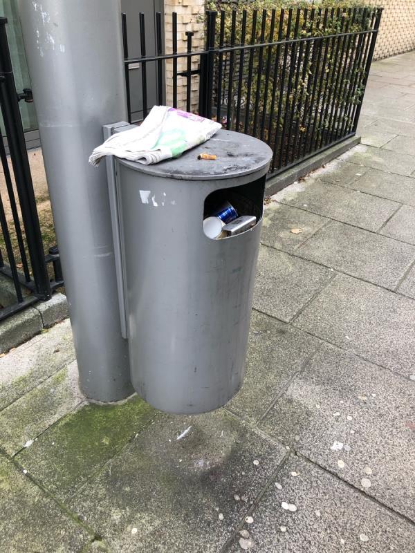 Bin overflowing opposite liberty bridge road doctors surgery next to bus stop-Henrietta Street, London, E20 1AS