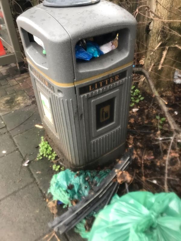 Grey public waste bin is overflowing at a bus stop on the A40 Western Avenue near Ribchester Avenue Ub6 -Western Avenue, London, UB6 8HL