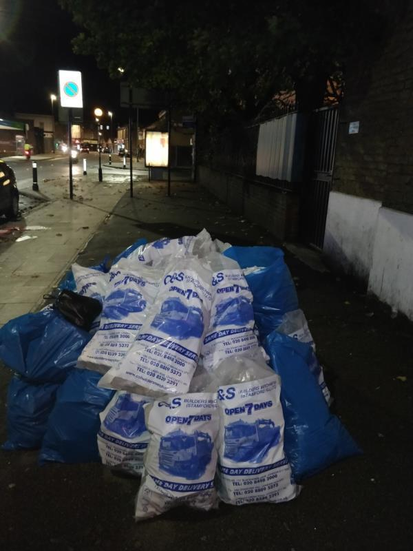 Dumped bags of construction waste materials on the pavement beside 104 Leytonstone Road E15-104b Leytonstone Road, London, E15 1TQ