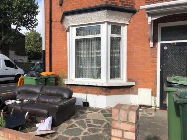 Unsightly rubbish in front garden with overflowing bins which are obstructed by sofas and inaccessible to refuse collection -53 Hatherley Gardens, East Ham, E6 3HG