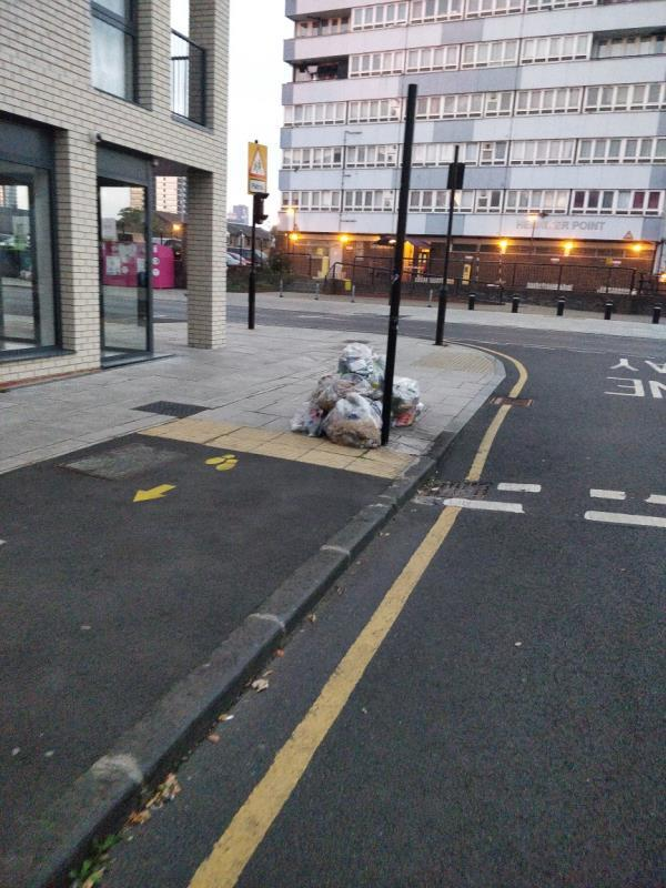 Sweeping bags of rubbish from yesterday on the pavement at the corner of Buxton and Leytonstone Road E15-60 Leytonstone Road, London, E15 1SQ