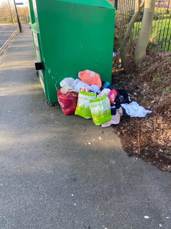 Large piles of bags of clothes (presumably now beyond use) dumped alongside the clothing bank outside Beckton District Park North -Tollgate Road, London, E16 3RX