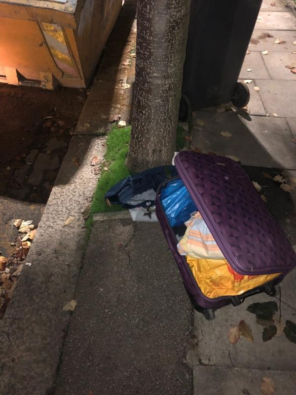 Suitcase dumped outside of 135 Effingham road by skip. Builders have also left bins in street-143 Effingham Road, London, N8 0AE