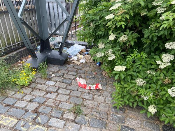 Litter by the foot of the pylon on the pavement -102 Tidal Basin Road, Canning Town, E16 1HW