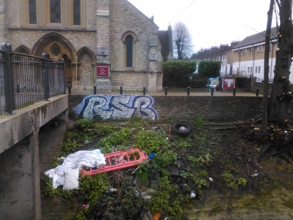 A duvet, pillows and a plastic barrier have been left on the river bank of the River Quaggy, opposite St Stephen's Church, 29 Lewisham High Street-29 lewisham high street