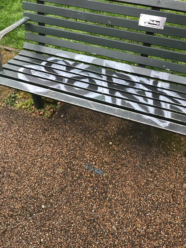 White and black spray painted tag is located on a green bench situated near lamp column MC1131 on Haven Green (footpath opposite Mount Park Road W5) -22 Haven Green, London, W5 2UP