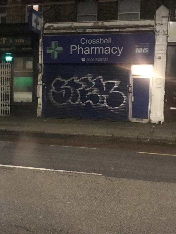 Very large spray painted tags are located on a blue shop shutter belonging to Crossbell Pharmacy 131 The Vale W3 -131 The Vale, London, W3 7RQ
