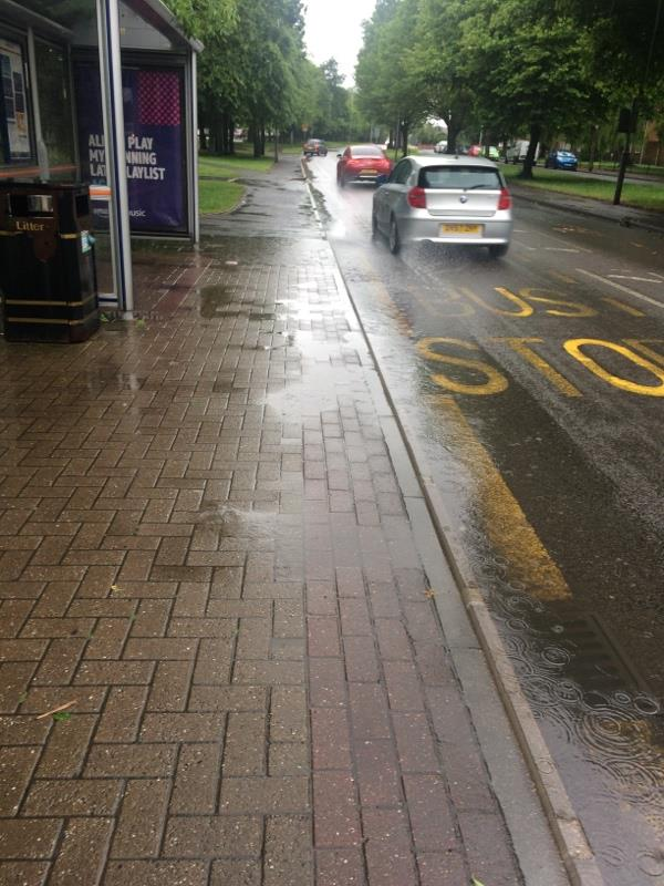 Blocked drain by Moathouse bus stop causing an unusable  shelter when weather is raining due to traffic spash-267A Lichfield Rd, Wolverhampton WV11 3EW, UK