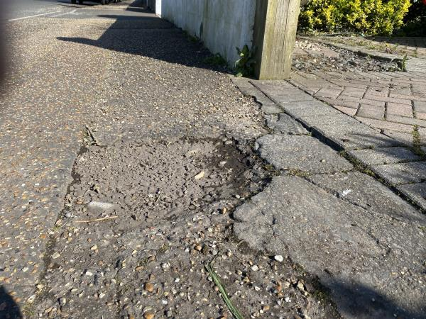Two potholes in the pavement outside the driveway of number 86 Brougham Road, Worthing, BN11 2NU-86 brougham road