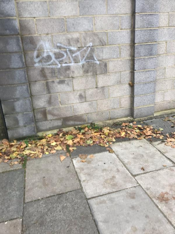 White spray painted tag is located on a brick wall on Green Man Passage junction Bayham Road W13-8 Bayham Rd, West Ealing, London W13 0TQ, UK