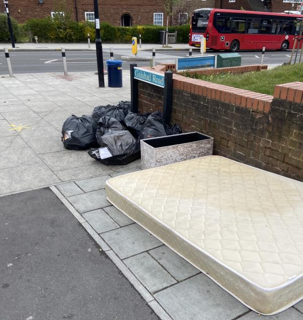 Mattress, around 5/6 rubbish bags, a bed frame and draws, a recycling bin, full of rubbish. A bag of rubbish strewn out on the grass-636a Downham Way, Bromley, BR1 5HN