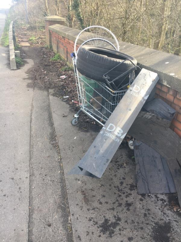 B&m trolly with tire and bike parts from halfords in business park flytipped over fence-B O C Ltd Rose Kiln Lane, Reading, RG2 0HS
