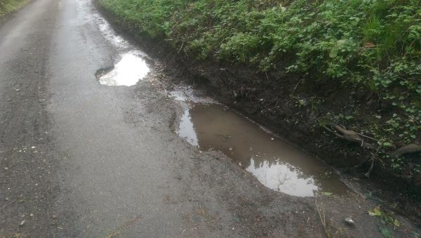Large and deep pothole at south edge of carriageway.  Real risk of wheel damage.-St Marys Parish Church Cray's Lane, Thakeham, RH20 3ER