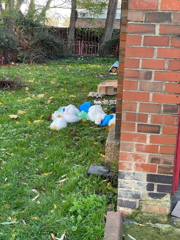 A number of bags have been dumped on the grass behind the stairwell that leads to then flats on the upper level-Kennedy Cox House Burke Street, Canning Town, E16 1EU