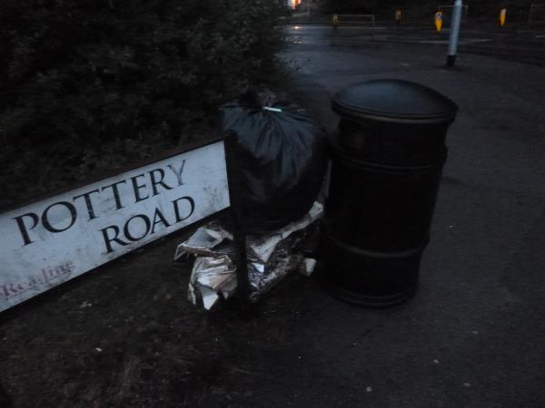 Broken insulation board and a sack of other rubbish recovered from the abandoned camp at the north west end of McIlroys Park, has been left by the litter bin in Pottery Road for ready for collection.-2f Pottery Road, Reading, RG30 6AH