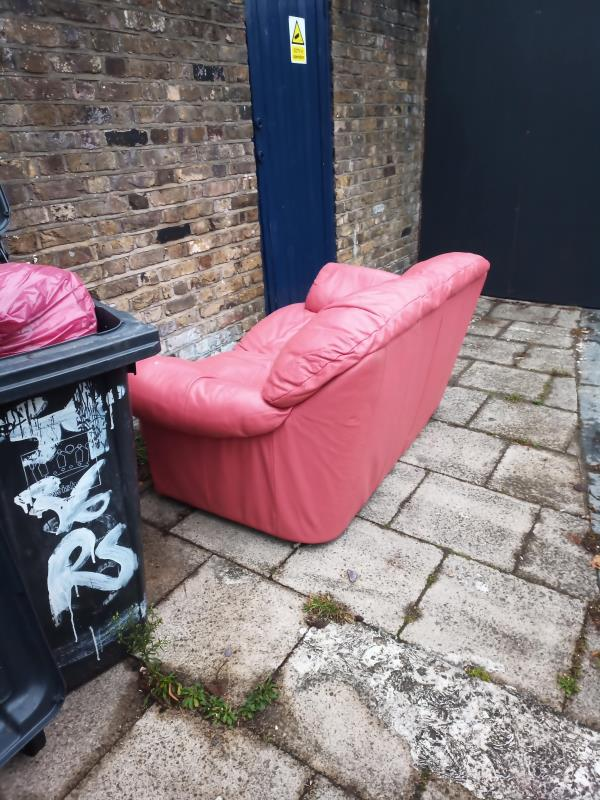 Fly-tipping of pink sofa on pavement. Located on Reginald Square, alongside brick wall, next to black rubbish bins. It's to the left side of a construction site, which has a grey painted wall. Item was left overnight.-36 Reginald Square, London, SE8 4RU