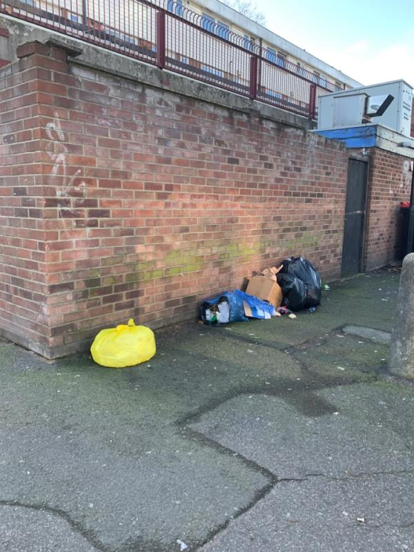 Bag of rubbish and crates dumped behind the barking road  shops-59a Barking Road, East Ham, E6 1PY