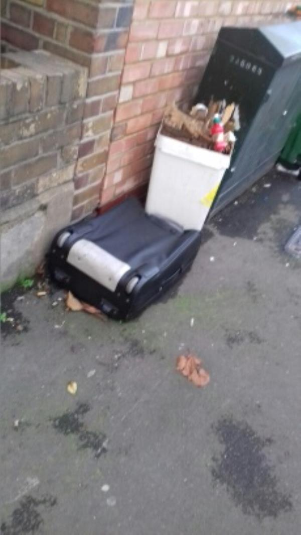 A travelling bag and a waste bin filled with rubbish dumped near 87 Wigston Road -87 Wigston Road, London, E13 8QN