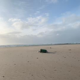 Wheelie bin in beach in front of sands. I can't move it on my own in this wind. -