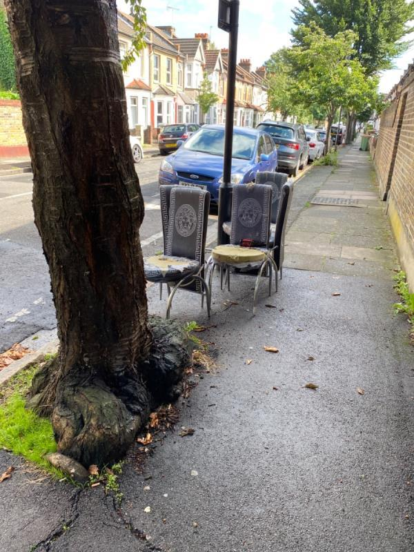 5 grey dining room chairs left by the tree near to the corner of Burford/Haldane roads. Also a blue buggy hood has been dumped right on the corner by the wall -104 Haldane Road, East Ham, E6 3JN