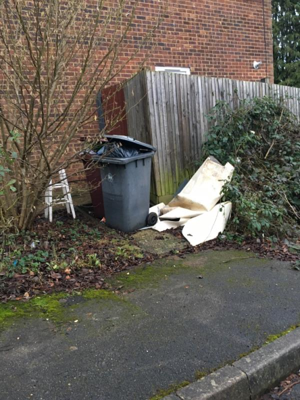 Old flooring. Not on private property, leaning against the fence on the pavement covered by vegetation.-22 Benson Close, Reading, RG2 7LP