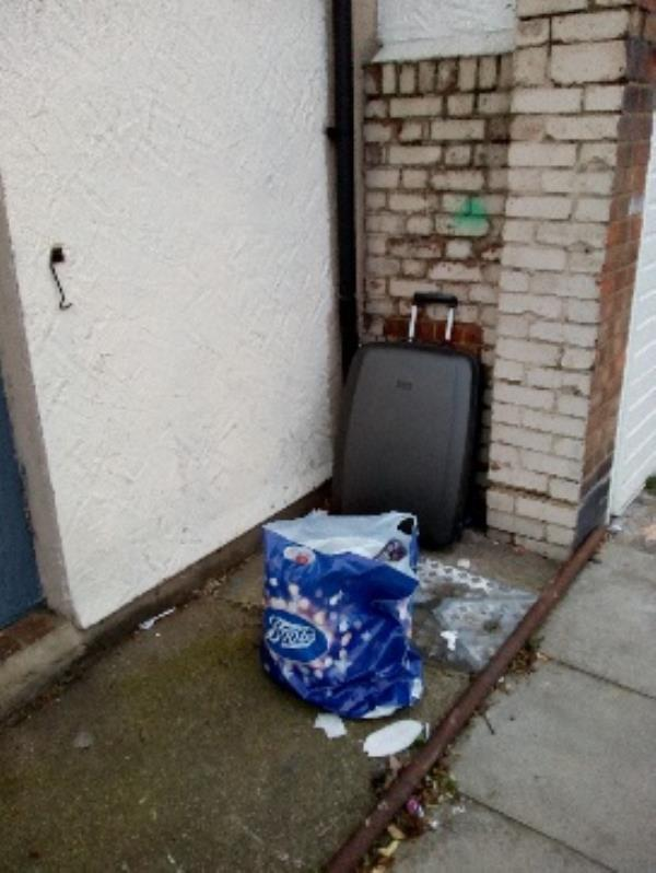 In Etherley Road N15  outside an empty building vetween 60 Etherley Road and the junction with Cranleigh Road N15 - a dumped suitcase and a bag of rubbish.-58 Etherley Road, London, N15 3AJ