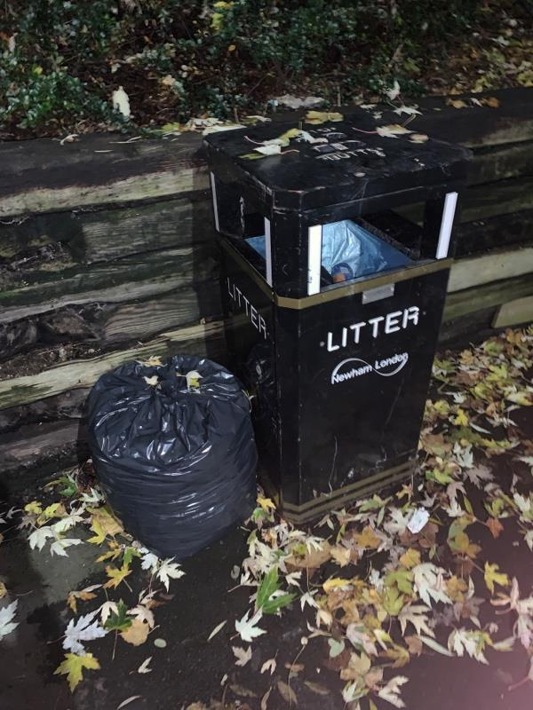 Bag dumped next to full bin on Mavis Walk at the intersection with Mitchell Walk-28 Leamouth Road, London, E6 5SG