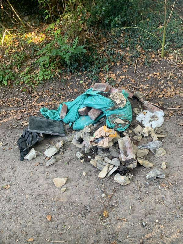 A lot of fly tipping, bricks, rubble, and a bike, obstructing a well used footpath and road -Junction Cottage Southcote Farm Lane, Reading, RG30 3DZ