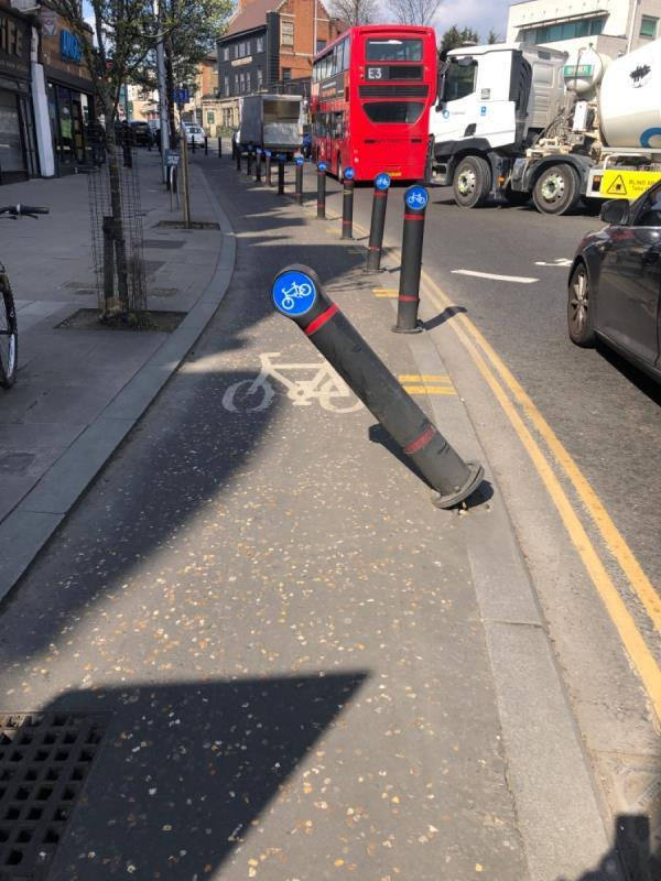 Cycle lane bollard bent over after accident -249 High Street, Acton, W3 9NX