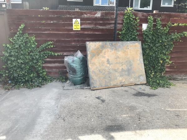 Heavy wooden board , a green sack of mixed rubbish and old piece of carpet.-Scout Hut Adjacent 25 Evesham Road, London, E15 4AL