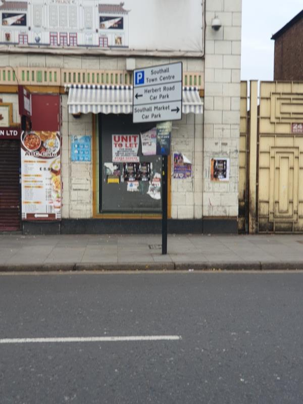 many posters on front of advert board-Southall Broadway (Stop N), Southall UB1 1RT, UK