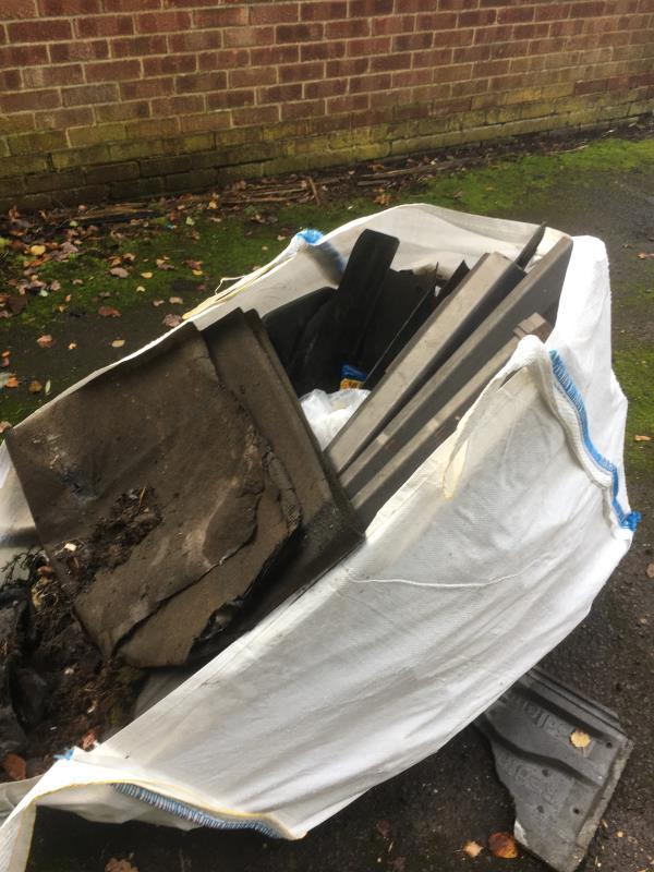 There is a large builders sack with old roofing and guttering dumped in a car park space in the service road behind Blackstone Close.-19 Blackstone Cl, Farnborough GU14 9JW, UK