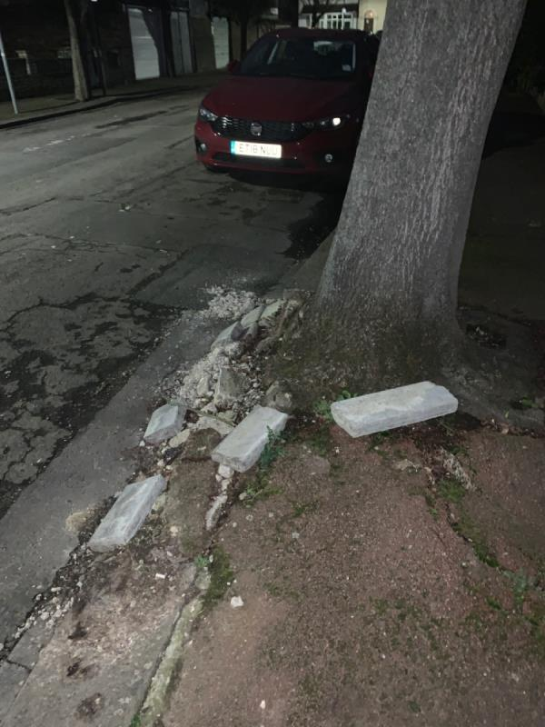 Kerb crumbling due to tree root. Debris on road. -5 Cumberland Road, London, E12 5AZ