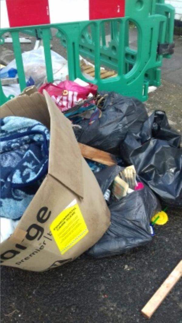 A cardboard box filled with clothings and several bags of wastes dumped near the highway materials outside 8 Dongola Road -11 Dongola Road, London, E13 0AY