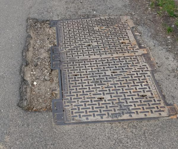 Large narrow but deep pothole adjacent to a Telecoms manhole, about 3ft from the road edge. Close to junction of West End Lane and Lawyers Lane.-Fuchsias West End Lane, Henfield, BN5 9RA