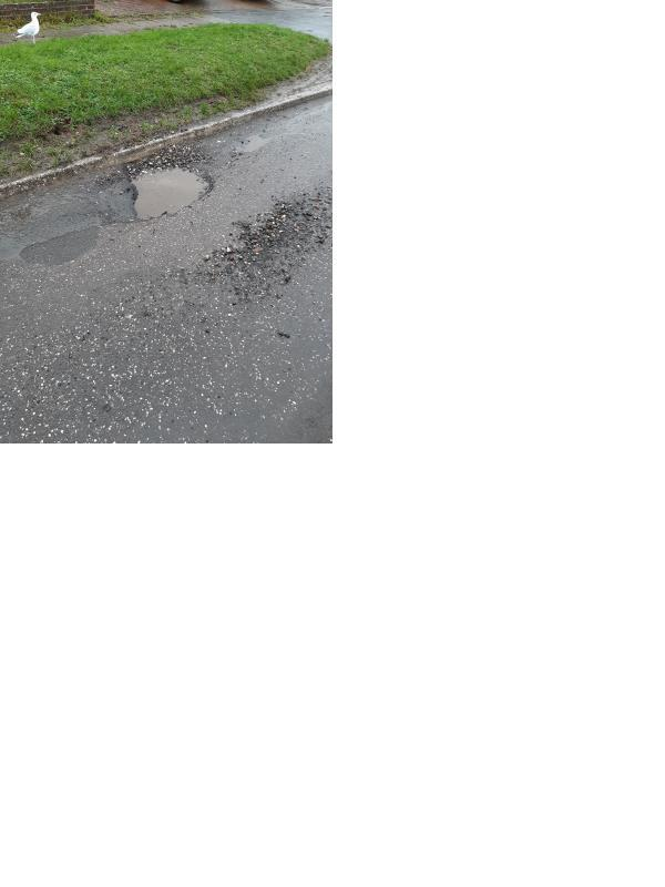 Pothole located near the curb on the road directly outside number 40 Fircroft Avenue, Lancing. image 1-40 Fircroft Ave, Lancing BN15 0NW, UK