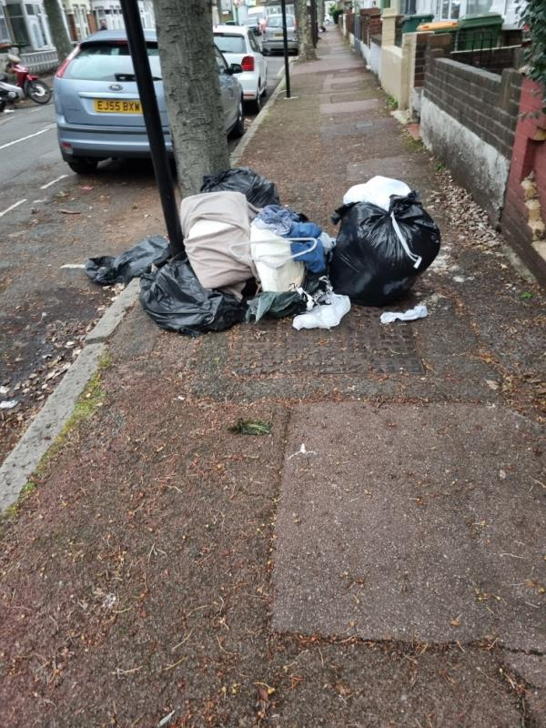 Household waste and clothes in black sacks with some torn spilling out food waste including raw meat. Has grown by two bags since last scene.-40 Latimer Ave, London E6 2LH, UK