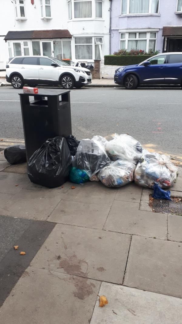 Bags of rubbish by the bin outside laundrette on the corner of Mafeking Ave and Central Park Road -234 Central Park Road, East Ham, E6 3DL