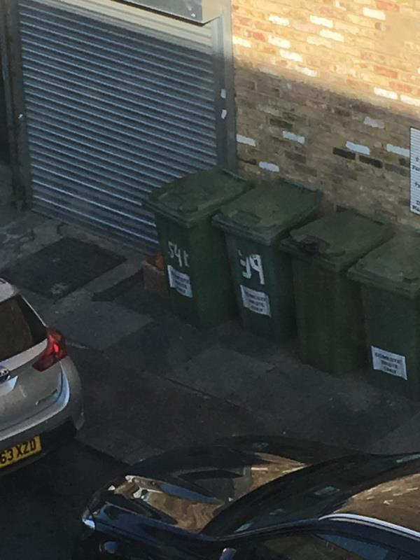 Pallet side of Coffee Hut and cardboard box other side of bins by garage. image 1-36 Plashet Grove, London, E6 1AE
