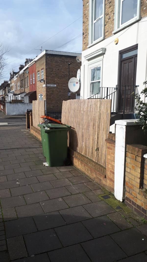 Partial footway obstruction by overfilled waste refuse containers belonging to 62A Chobham Road. These are permanently stored on the footway.-60 Chobham Road, London, E15 1LU